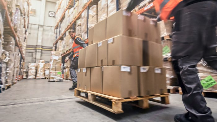 Two workers moving a palette of boxes within a warehouse