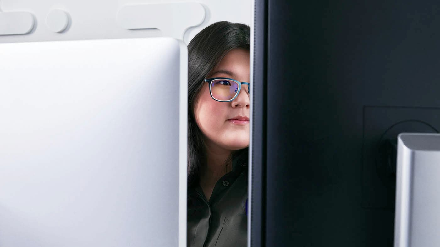 Woman sitting in front of computer monitor