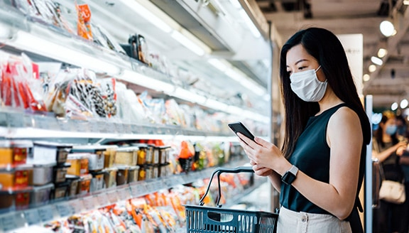 Shopper standing in front of cold food shelf using their smartphone