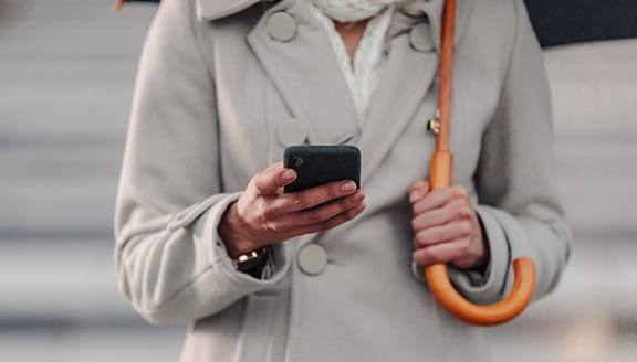 Person in winter coat using their smartphone