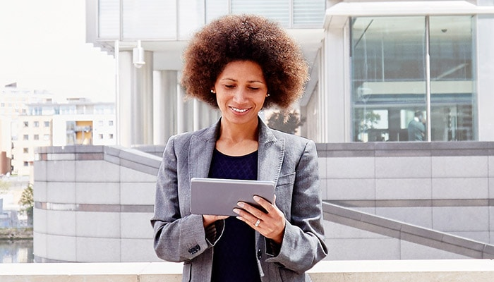 Woman looking at tablet computer outside office building