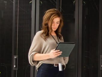 Woman looking at pad in server room