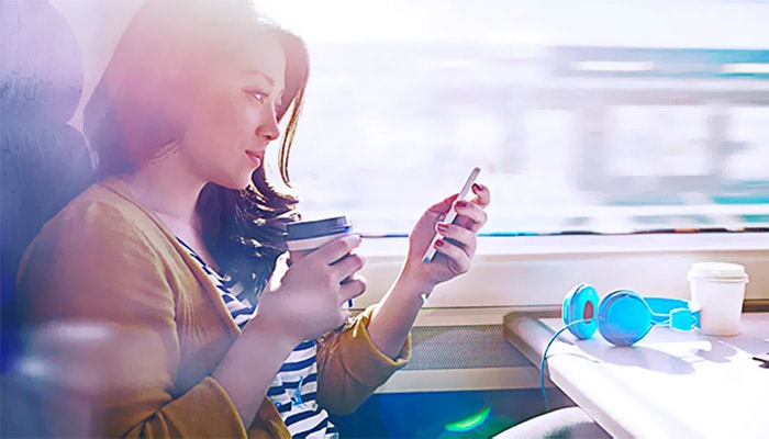 Woman sitting on train holding coffee and looking at mobile phone