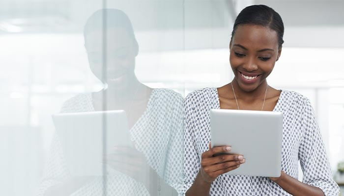 Smiling woman looking at tablet in the office
