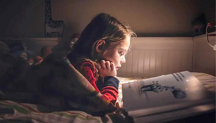 Child reading a book in bed by night light