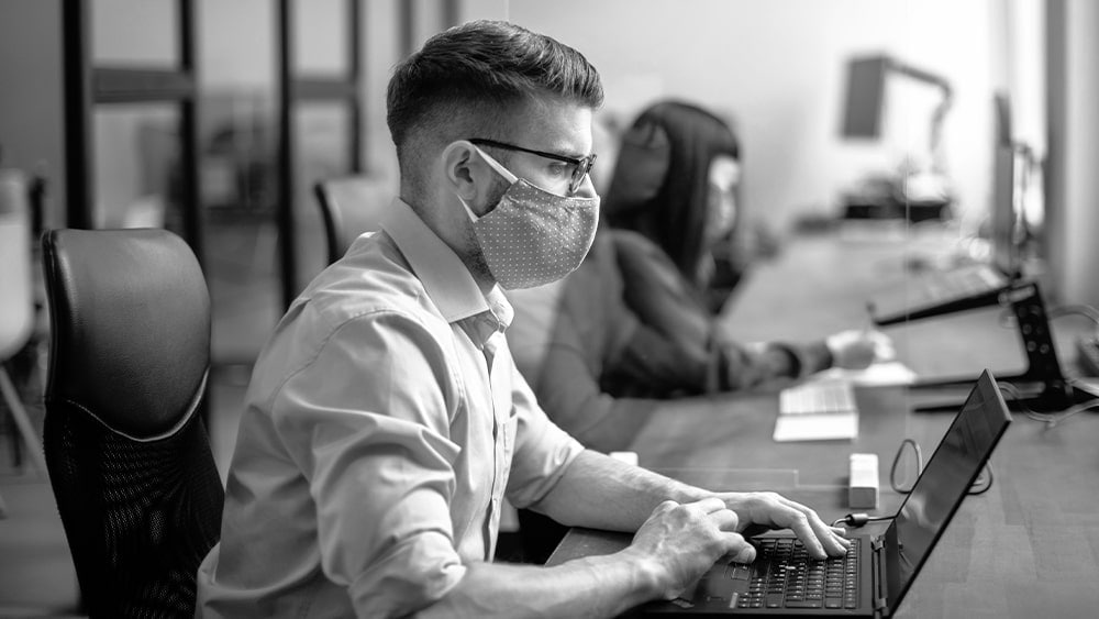 a man wearing mask working on the laptop