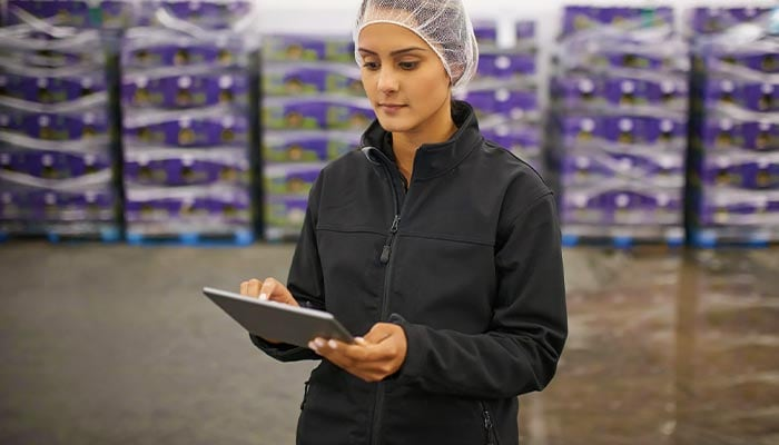Woman accessing a tablet on a stockroom floor