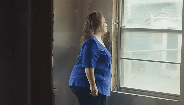 Woman in a blue shirt looking out a window