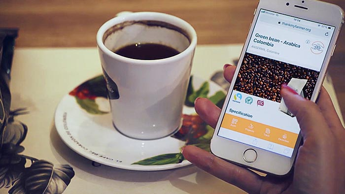 Close up of a person's hand scrolling past coffee beans on a smart phone next to a cup of coffee