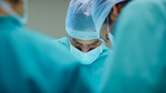 Closeup photo of 3 surgeons operating
