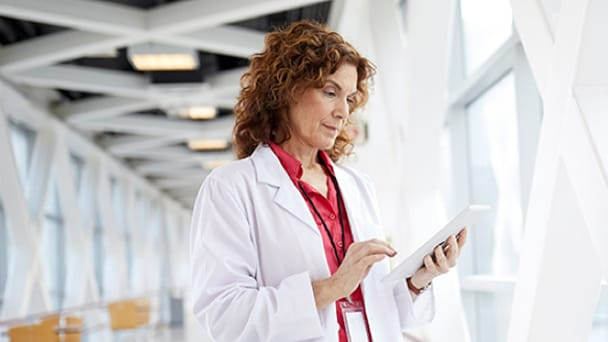 Medical professional standing in a glass hallway looking at a tablet
