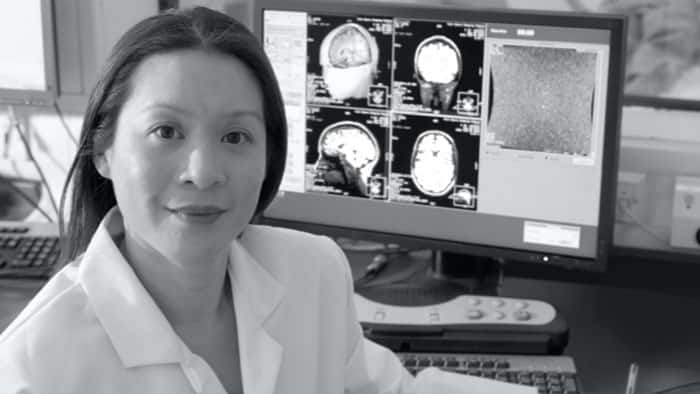 A health professional looking at the camera with a screen of imaging studies behind her