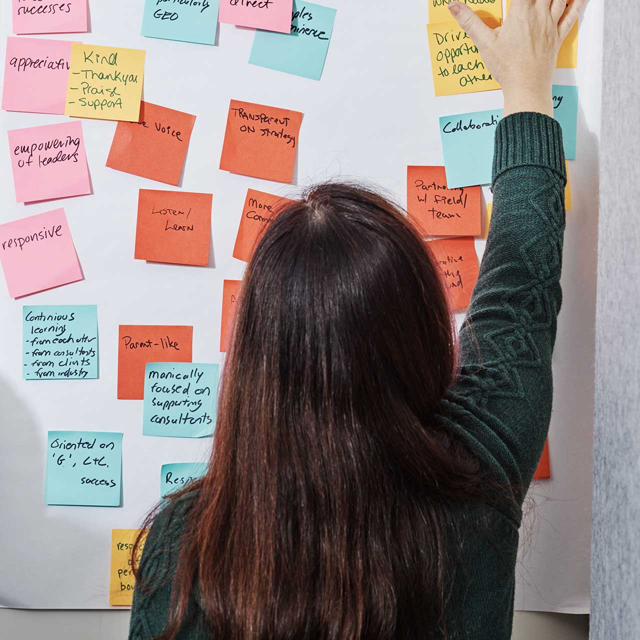 Woman putting sticky notes on white board.