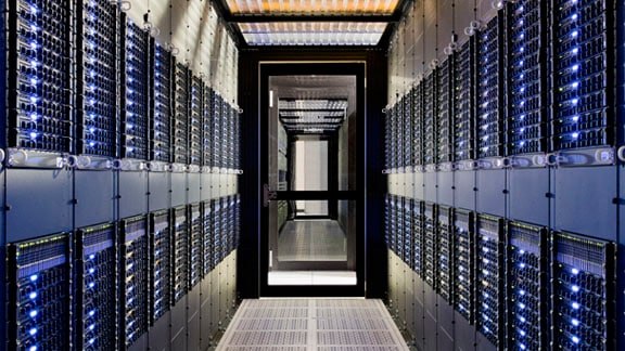 View of server room lined with computers on both sides of the aisle