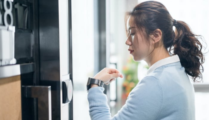 Woman using smart watch to enter secure location