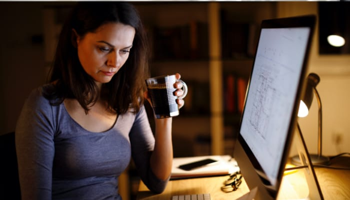 Woman with a glass of coffee with in front of monitor screen