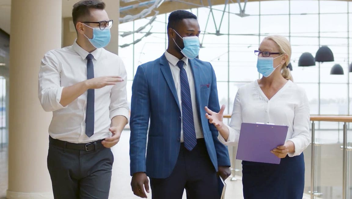 Three people in formal clothes talking to each other at office using face masks