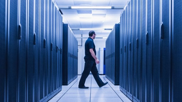 Technician walking across corridor in server room