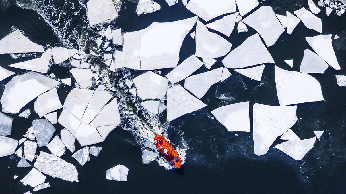 aerial view of ship sailing through ice formations