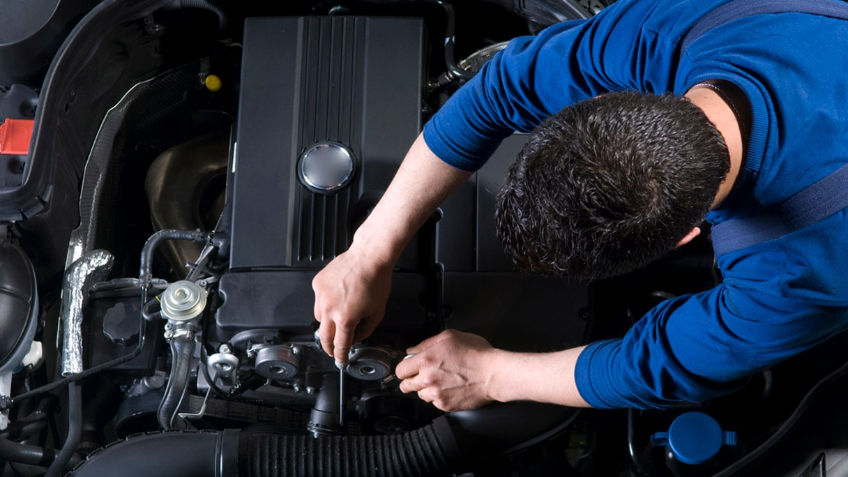 overhead view of mechanic working on car engine