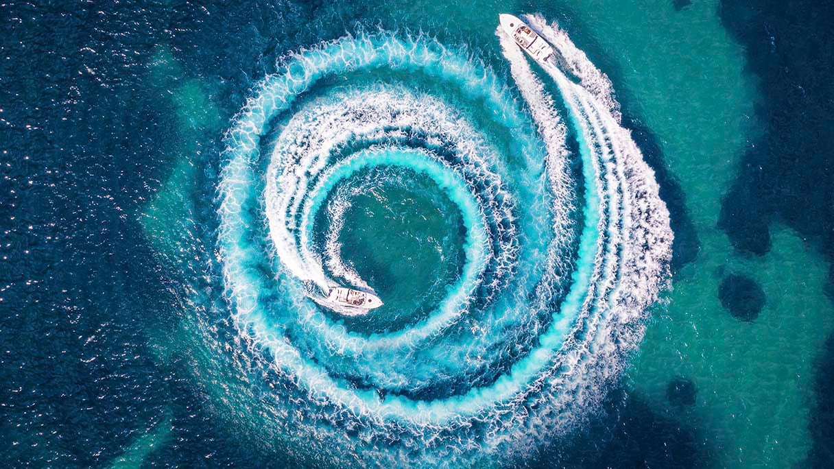 aerial view of 2 speed boats sailing in circles