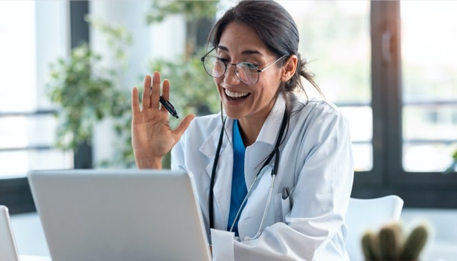 Female doctor waving and talking with colleagues through a video call with a laptop during  consultation