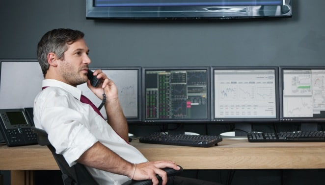 Exchange broker in front of monitor display speaking on phone