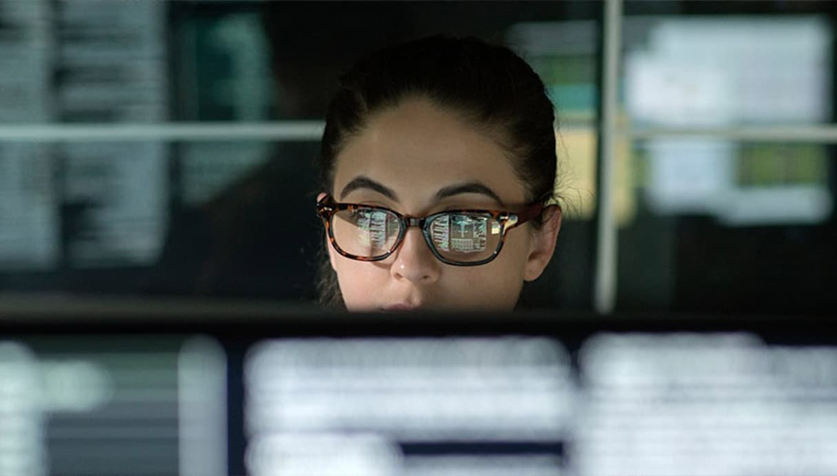 Person with glasses looking at a computer