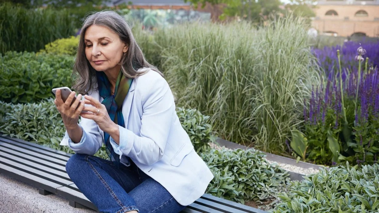 Woman sitting on bench looking at her mobile phone