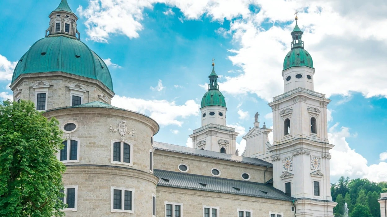 Large interconnected structures and three sea green domes with spires on the top of the beautiful Archdiocese Salzburg