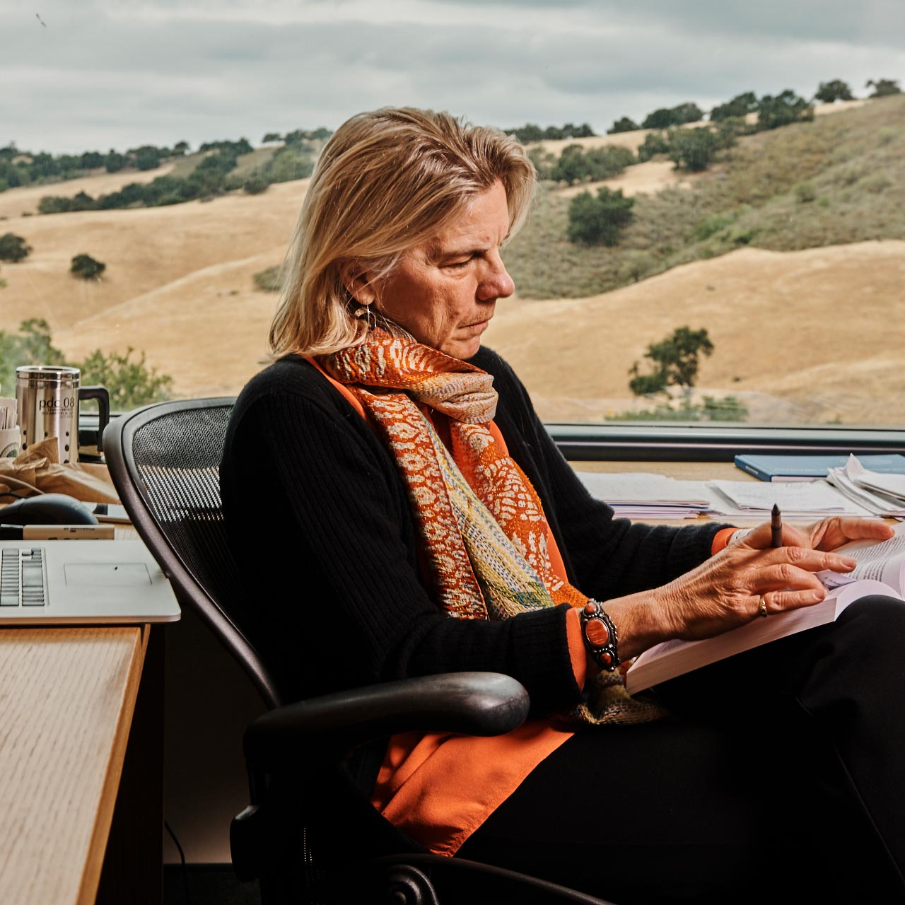 businesswoman sitting at desk reading book on her lap