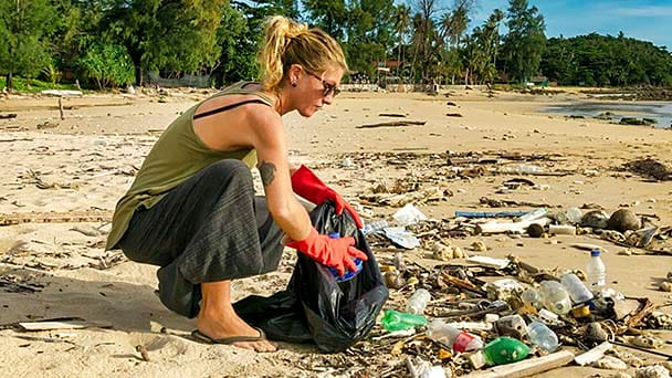 person cleaning up litter from a beach