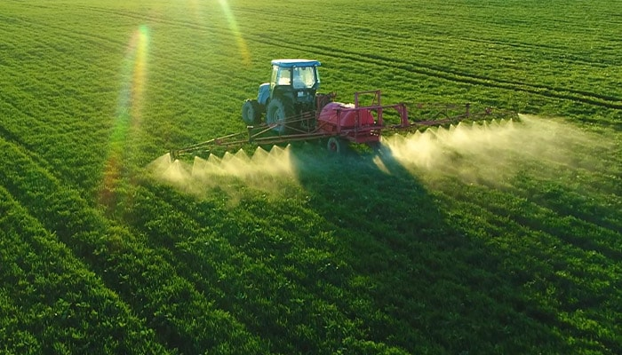 Tractor spraying a farm field