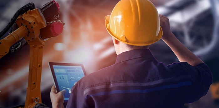 A man with a hardhat working using a tablet