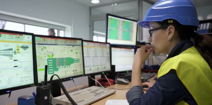 A woman using a hardhat looking on a monitor