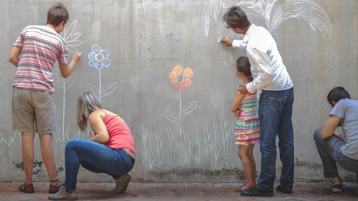 a group of people painting a wall with crayons