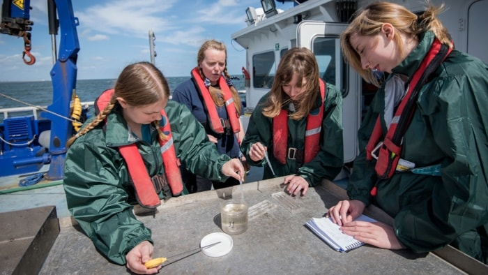 Four woman doing water laboratory test in a boat