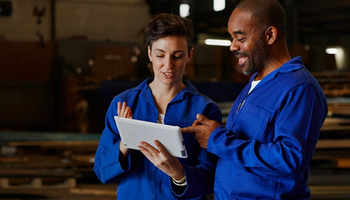 Woman holding a tablet and talking to a man in a warehouse