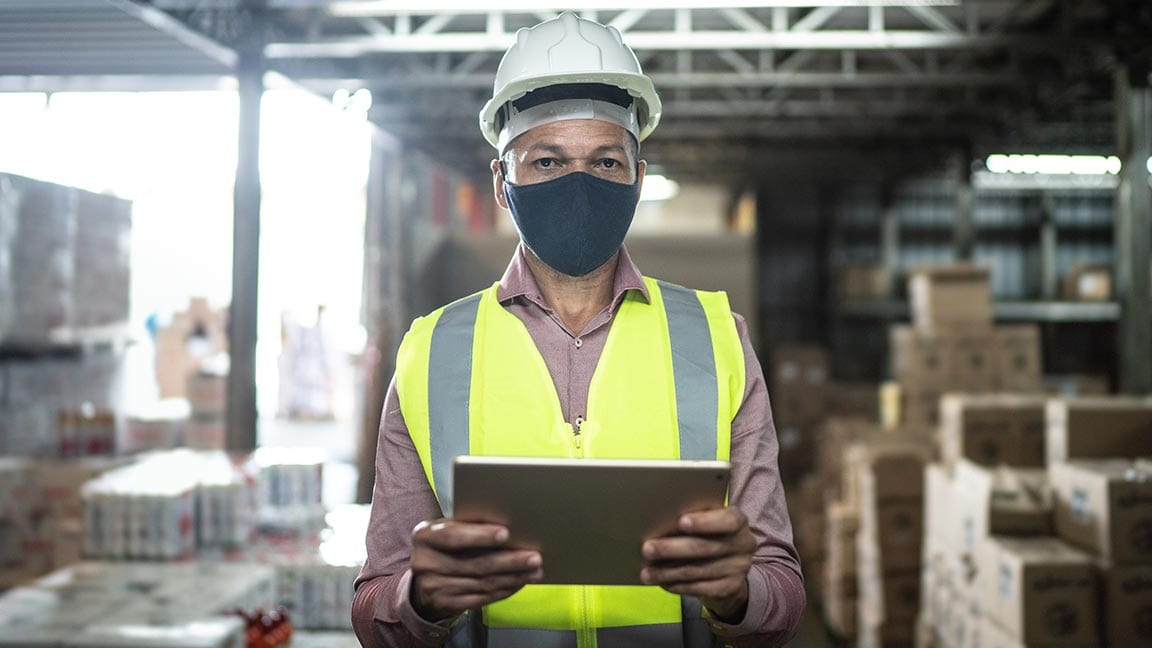 Worker wearing mask and safety equipment holding tablet in warehouse