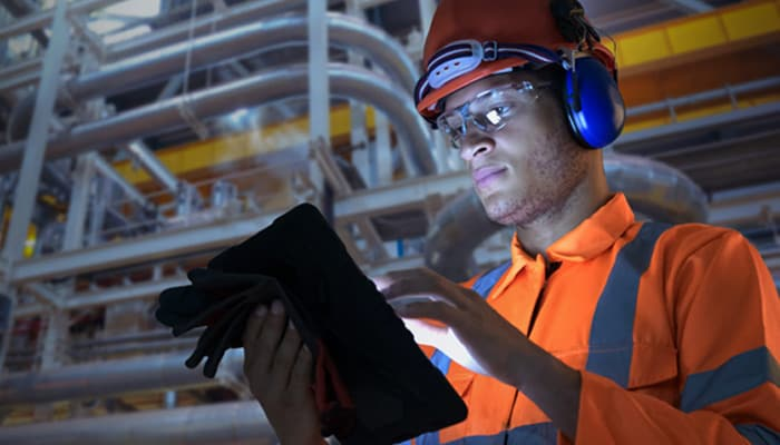 Man with hard hat using a tablet