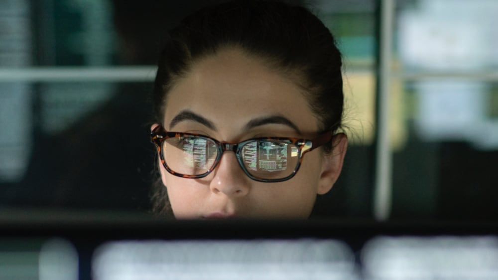 close up on woman's glasses reflecting a computer system