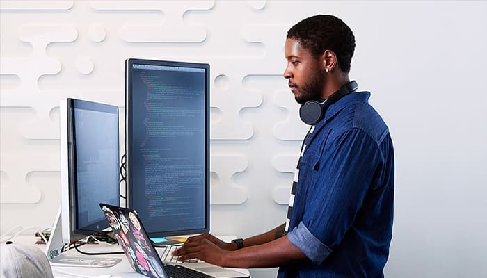 Man using a computer on multiple screens