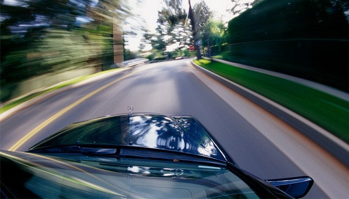 Car driving fast down a road from a first-person vantage point