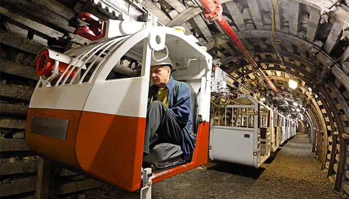 Man controing machinery in an underground tunnel