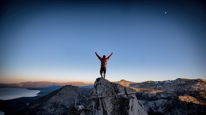Person standing on mountain peak with arms in the air