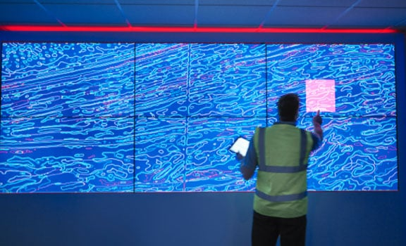 Business person reviewing information on an electronic wall
