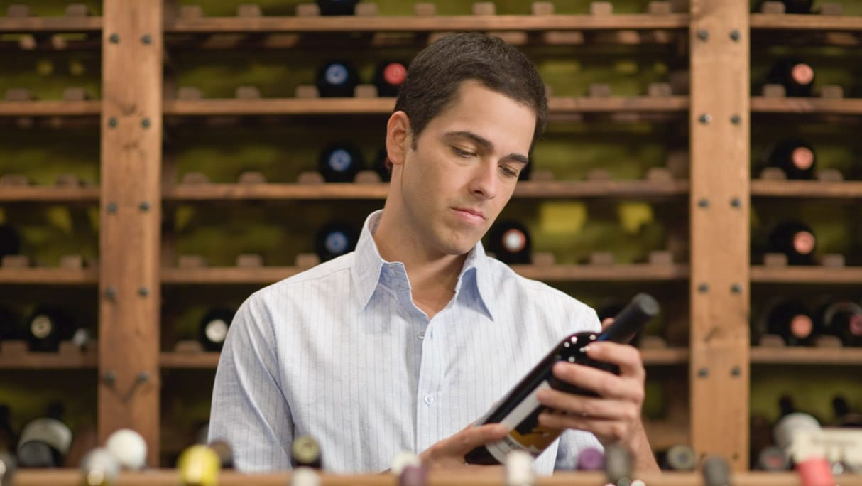 Person choosing a bottle of wine