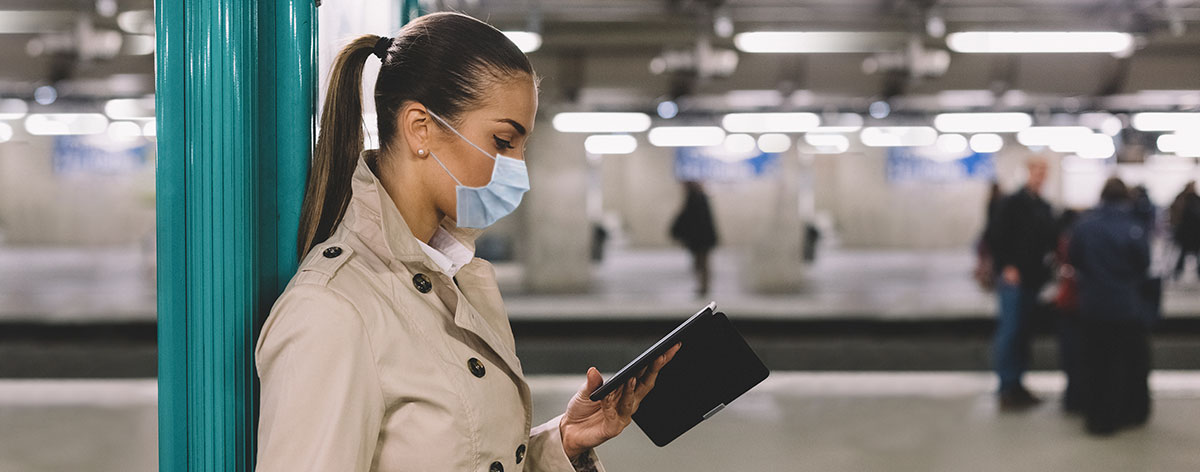Woman wearing a face mask using smartphone at subway station