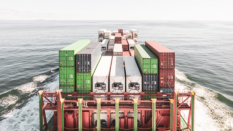 A view of stacked shipping containers, as seen from the bridge of a sailing transport vessel