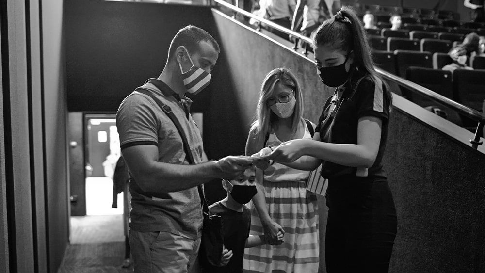 three people wearing masks in a stadium